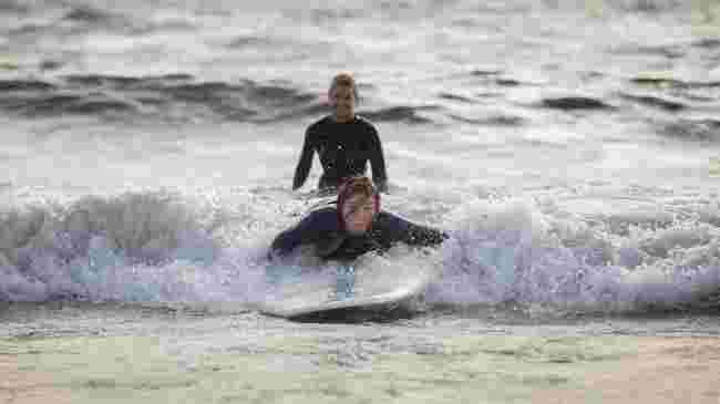 Camilla ligger på brettet i bølgene.