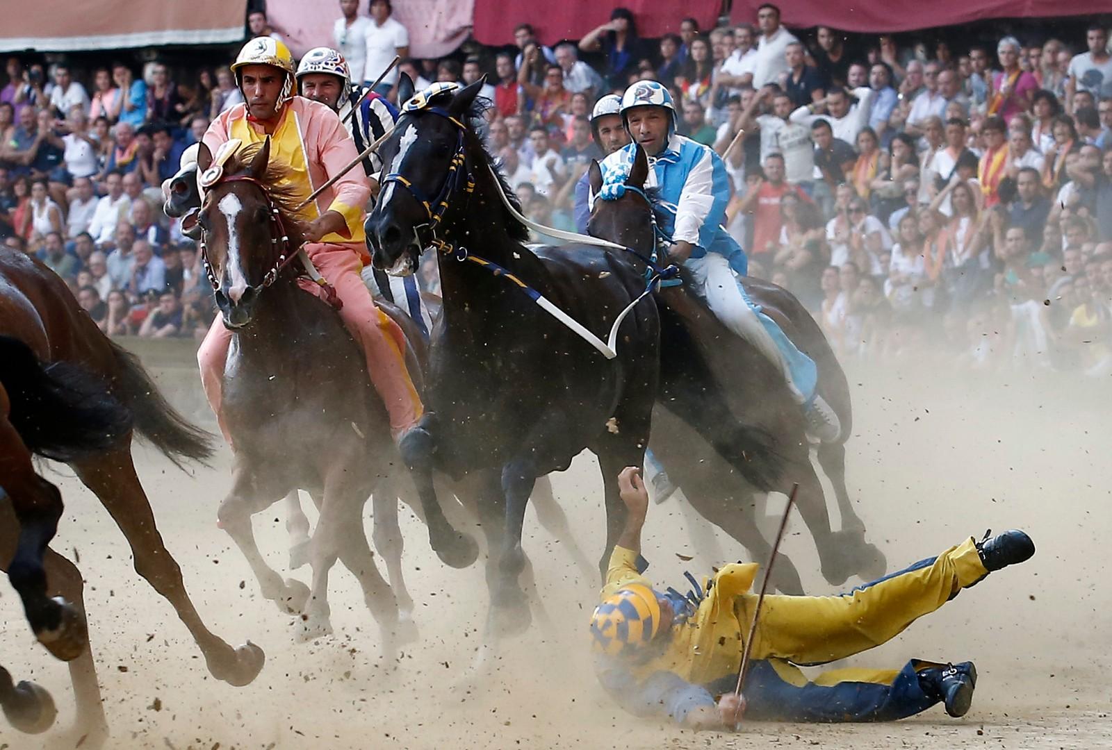 En rytter faller av hesten i det tradisjonelle Palio av Siena-rittet. Rittet foregår på hest uten sal, og er regnet for å være ganske tøft.