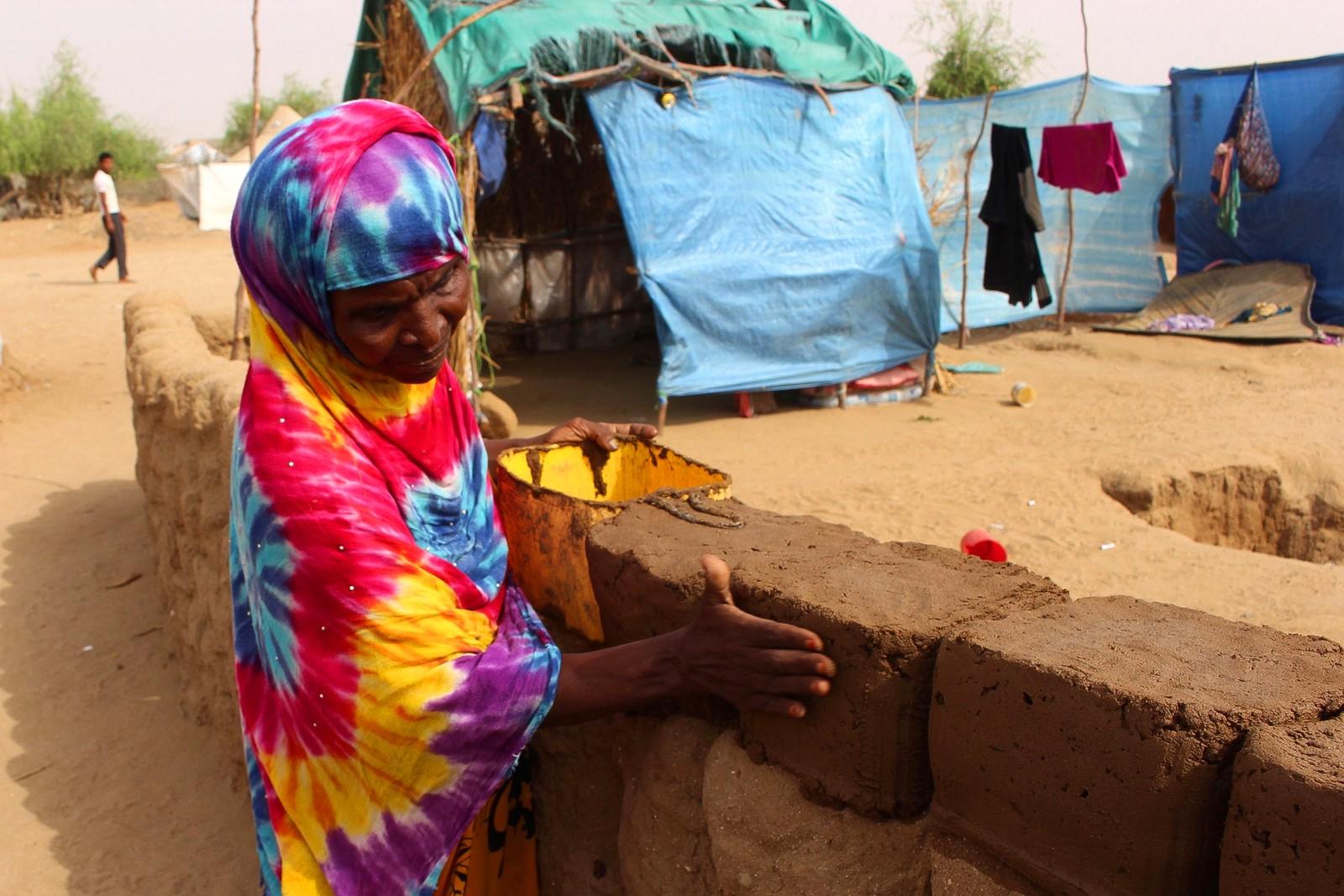 En kvinnelig flyktning fra Yemen bygger en mur av leire i en leir i Hajjah i Yemen.