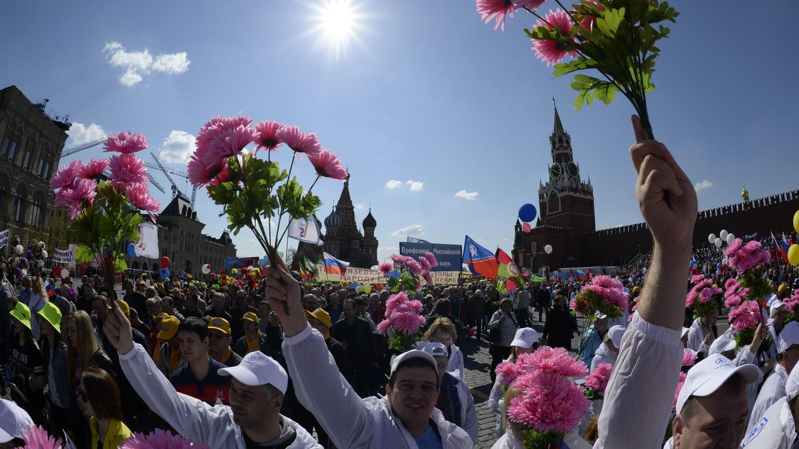 Russiske fagorganiserte holder opp blomster, flagg og ballonger under en parade på Den røde plass i Moskva, søndag.