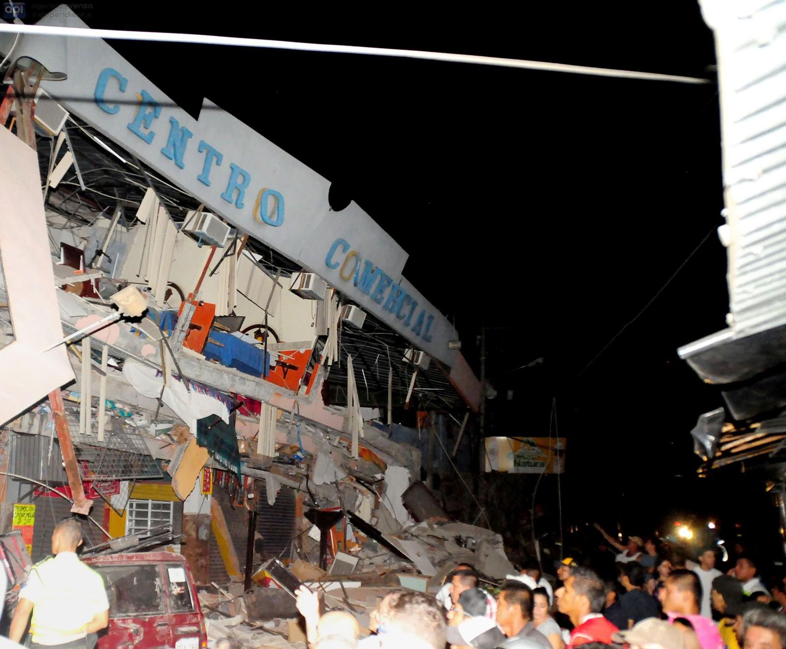Redningsarbeidere jobber med å få mennesker ut av en sammenrast bygning i byen Manta etter skjelvet.