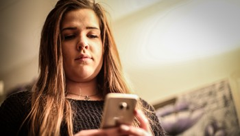 Marita Sofie Olaussen holder en mobiltelefon i hendene