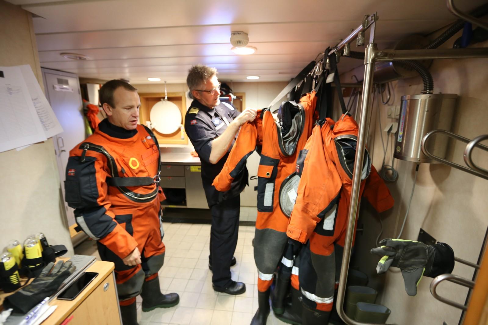 FLYTEDRAKTEN PÅ: Vaktsjef og takkeloffiser Andreas Marstrander (til v.) og operasjonsoffiser Gunnar Dyngeland kler seg om til patruljetokt i garderoben. Overlevingsdrakter er påbudt når de skal ut i lettbåten.