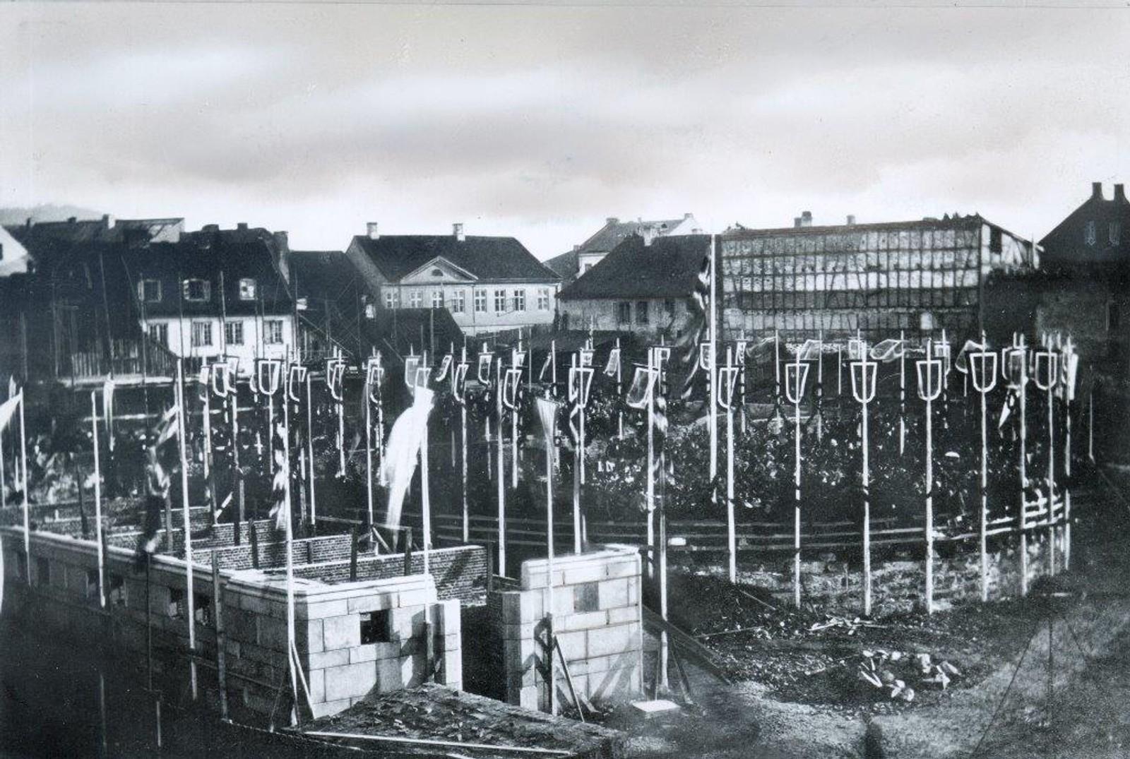 Grunnstenen til Norges Storting ble lagt 10. oktober 1861 i en høytidelig seremoni. Bygningens omriss er markert med flagg, vimpler og blomster. I fundamentet under det som skulle bli presidentpodiet ble det plassert en eske med sølvmynter fra samme år. Foto: Ukjent / Stortingsarkivet / NTB scanpix