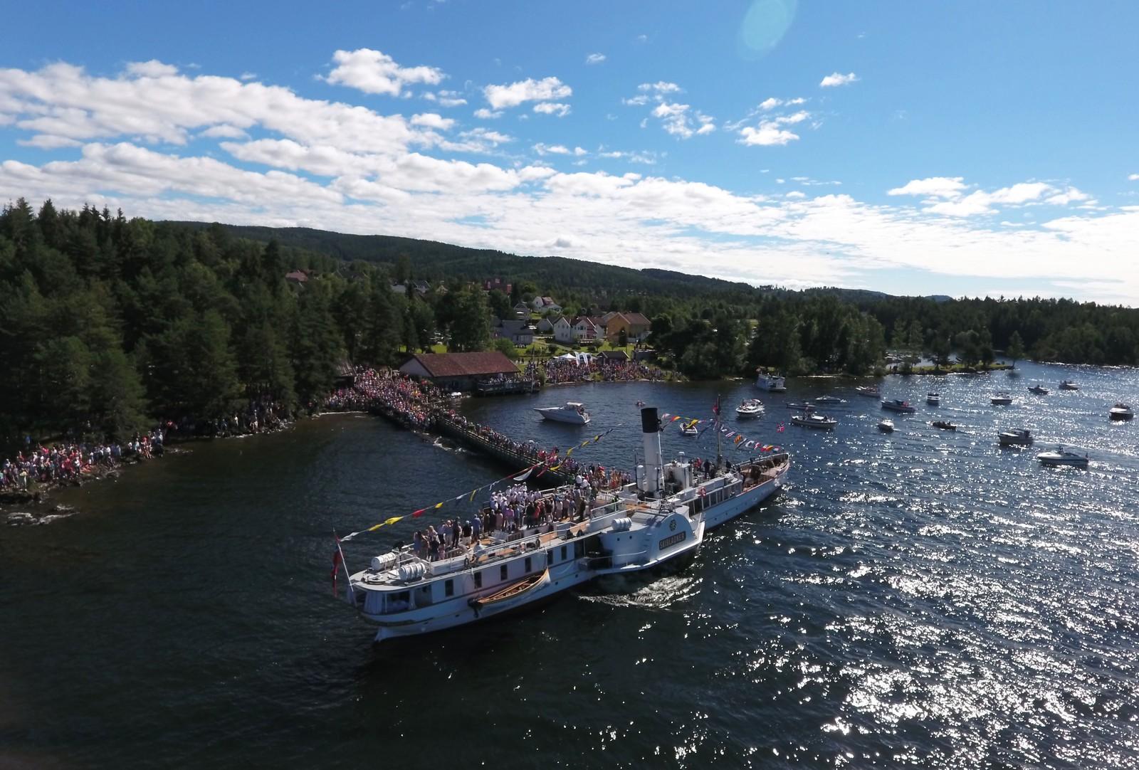 Skibladner ligger inntil brygga i Moelv med en stor menneskemengde på land.