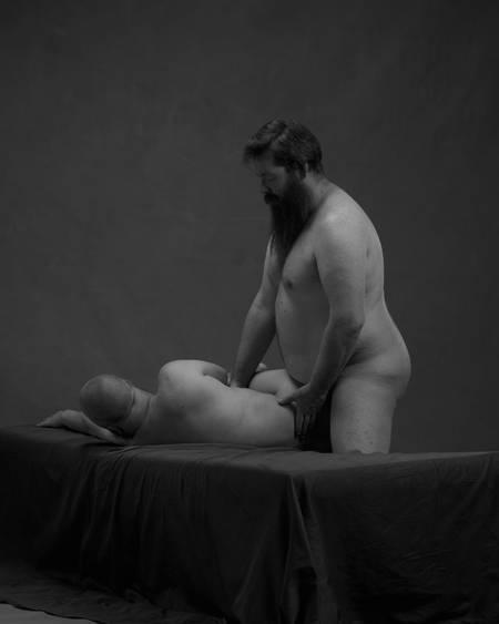 En naken mann ligger på siden på senga med en annen naken mann stående bak rumpa hans.