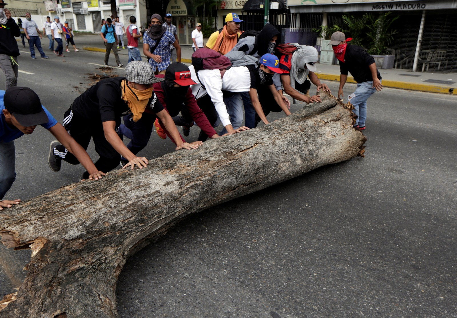 Demonstranter blokkerer veien med en trestamme.