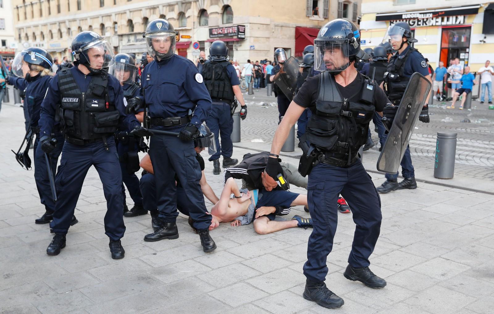 Politiet legger en fotballsupporter i bakken.