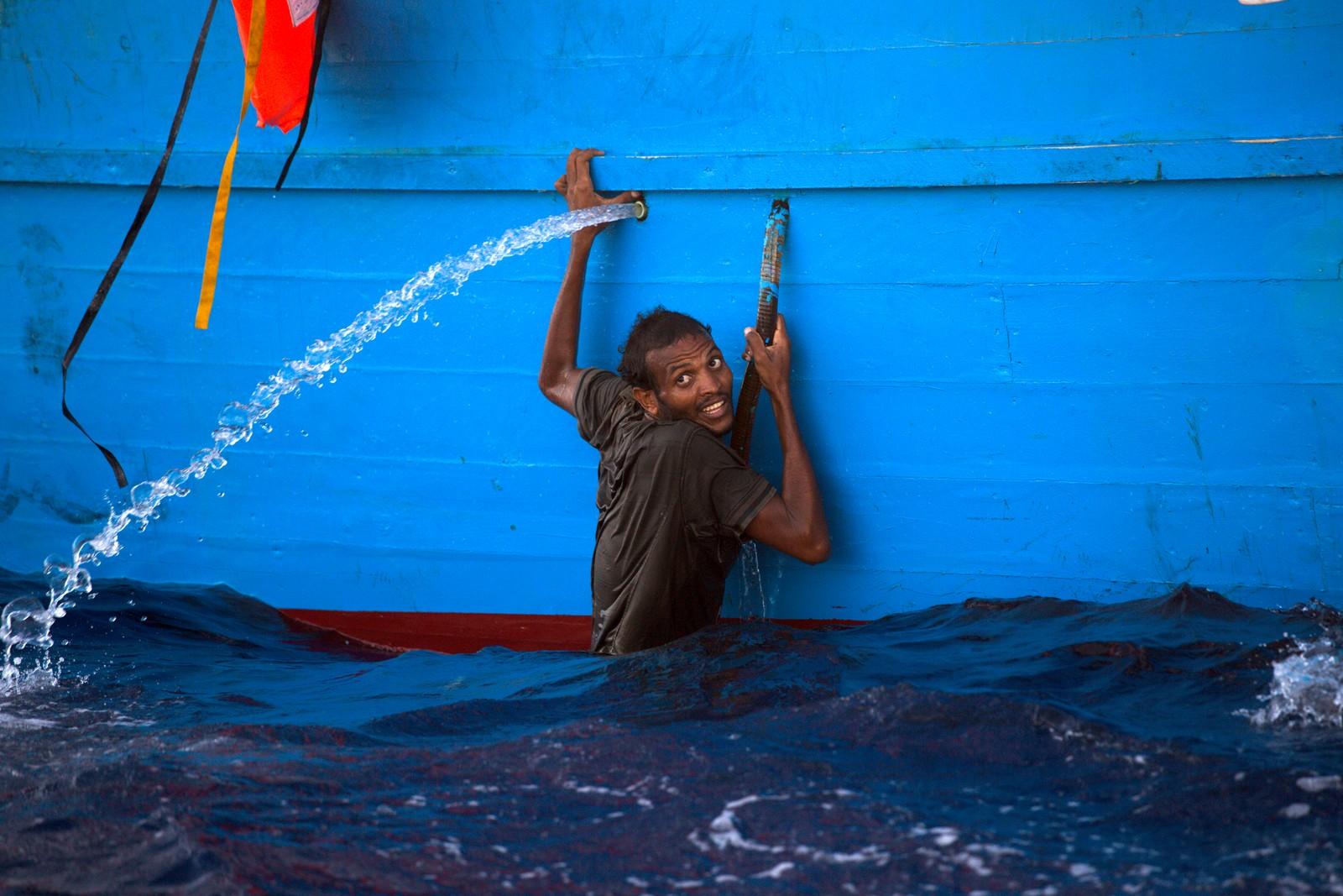 """En mann klamrer seg til en overfylt båt etter å ha hoppet i havet under en redningsaksjon i Middelhavet den 29. august. Flere tusen flyktninger ble reddet av den spanske frivillige organisasjonen """"Proactive Open Arms"""". De hadde mer enn 20 båter i aksjon denne dagen."""