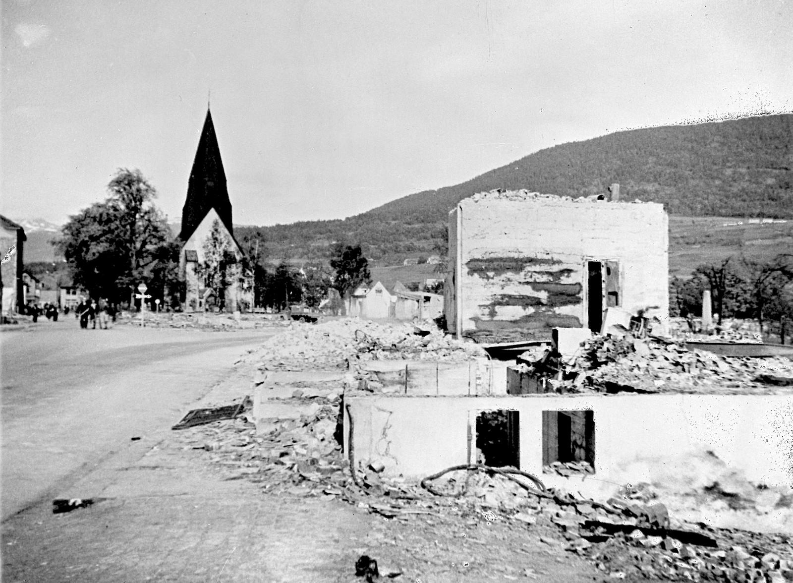 Bygninger ligger i ruiner i Voss etter tyske luftangrep. Voss kirke sees i bakgrunnen.