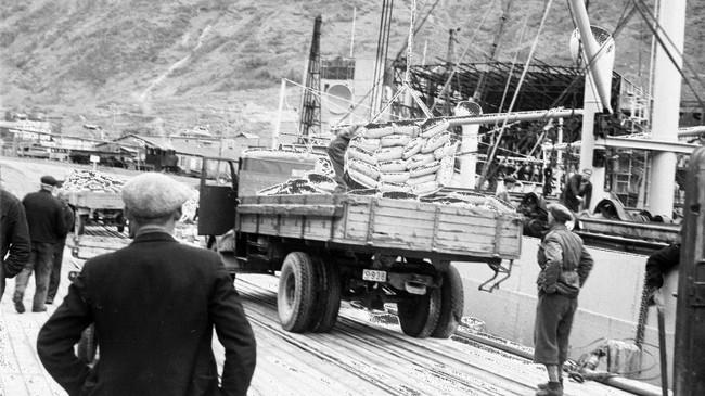 """Eit historisk bilete. Den første oksidlasta kjem til Årdalstangen med DS """"Ørnefjell"""" i 1947, og produksjonen av aluminium kan ta til. Foto: Verksposten. Eigar: Årdal Sogelag."""