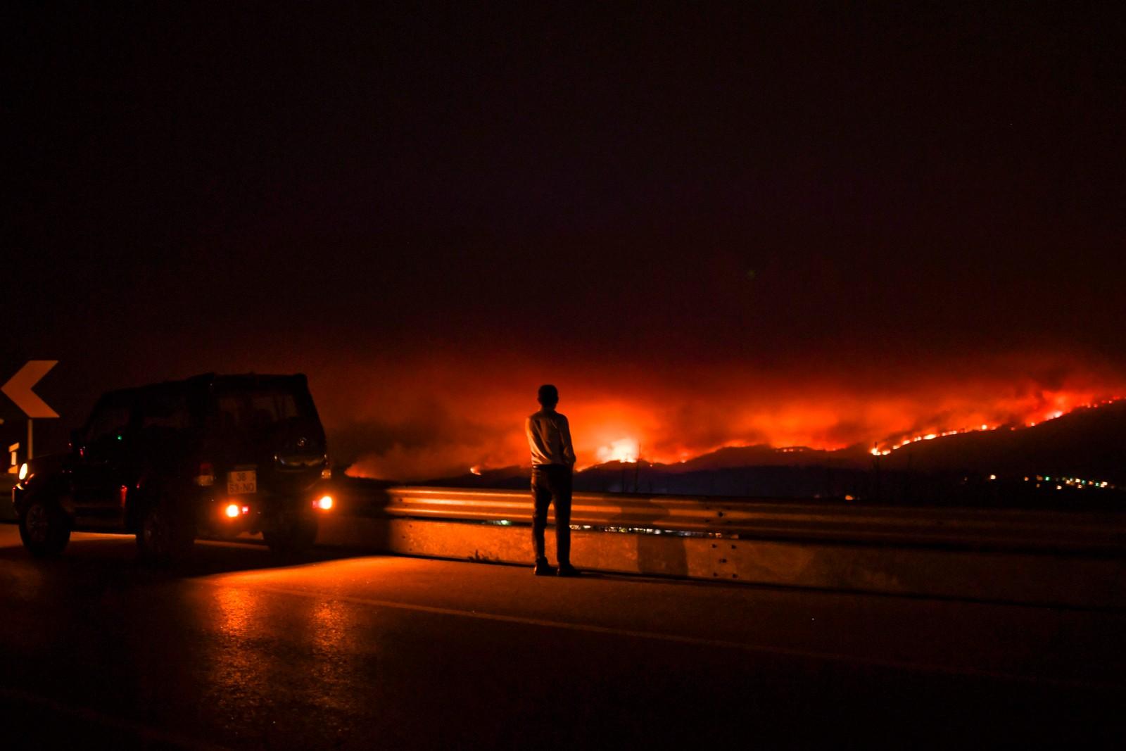 En mann følger brannen i Anciao.