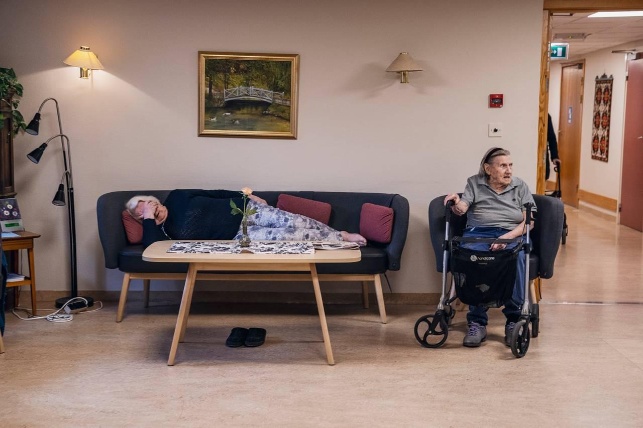 Anne Marie har lagt seg langflat på sofaen med hånden foran øynene. Ved siden av sitter Eugenie i en stol med rullatoren sin foran.