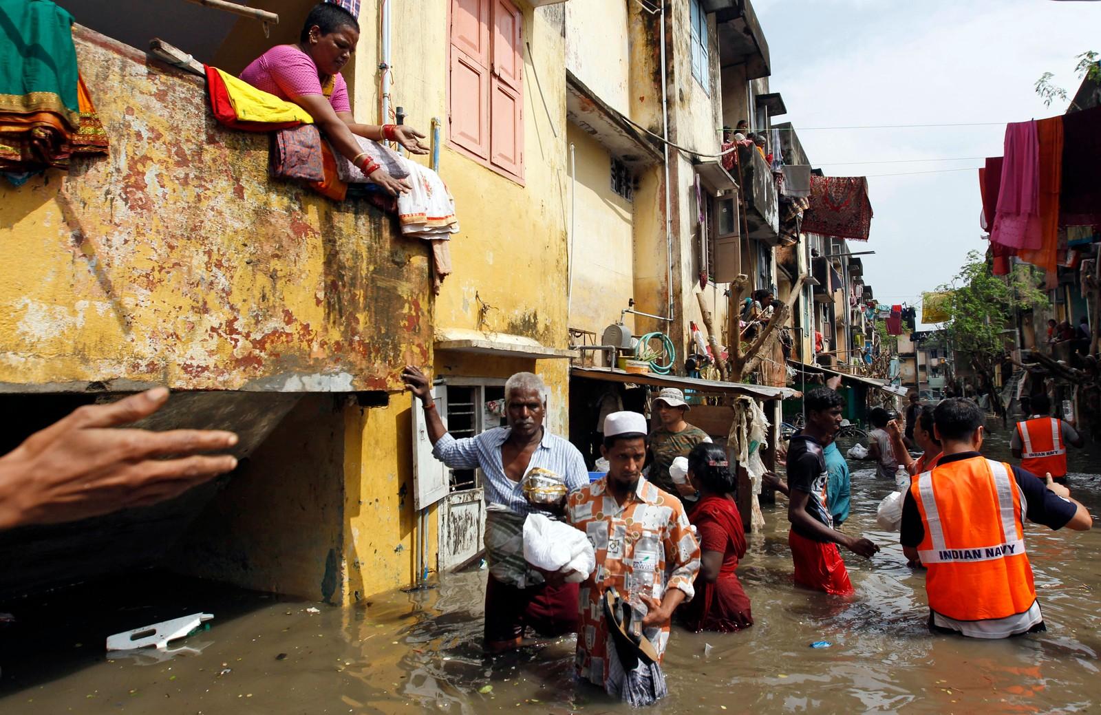 Flomrammede mennesker får matpakker av marinen. Dette er det kraftigste regnfallet på hundre år i delstaten Tamil Nadu i India.