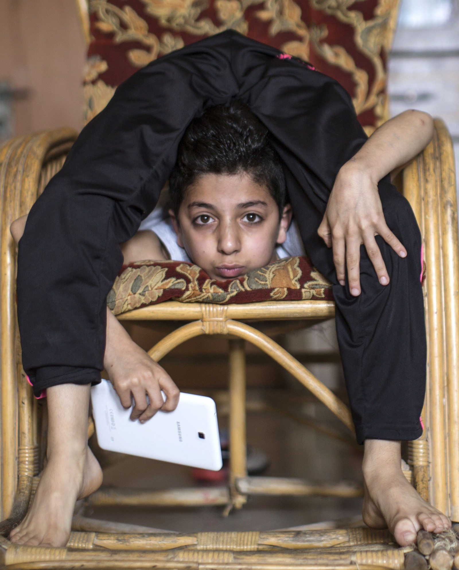 Palestinske Mohammed al-Sheikh (12) drømmer om å slange seg inn i Guinness rekordbok. Her imponerer han nyhetsbyrået AFPs fotograf mens han sjekker nettbrettet.