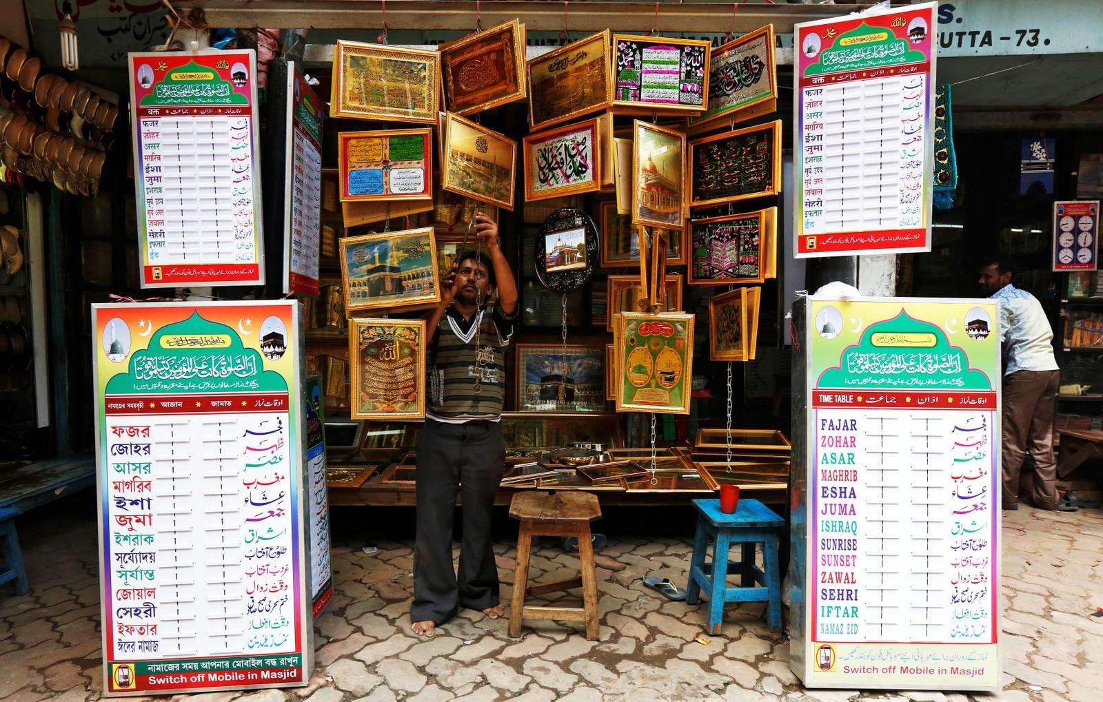 En butikkansatt henger opp religiøse bilder for salg i Kolkata i India. India har over 170 millioner muslimer, noe som utgjør 14 prosent av befolkningen ifølge en folketelling i 2011.