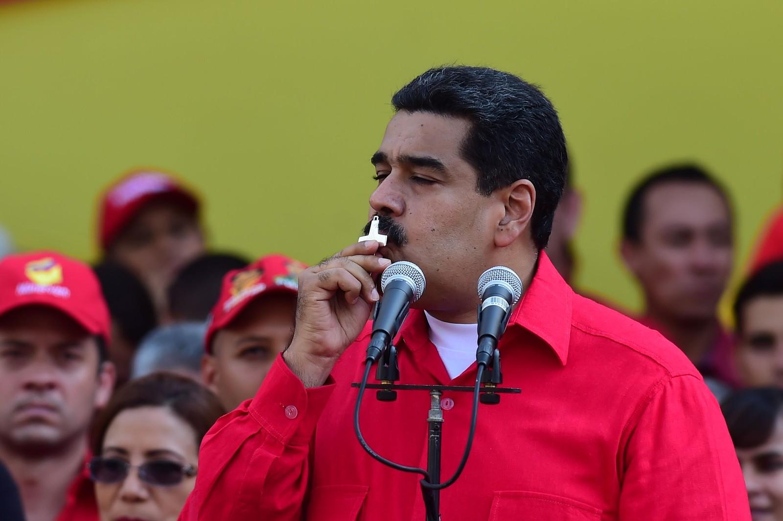 Venezuelas president Nicolas Maduro har ikke gitt opp kampen om å beholde makta på tross av krisa i landet. Her kysser han et kors under en tale til sine tilhengere i hovedstaden 25. oktober.