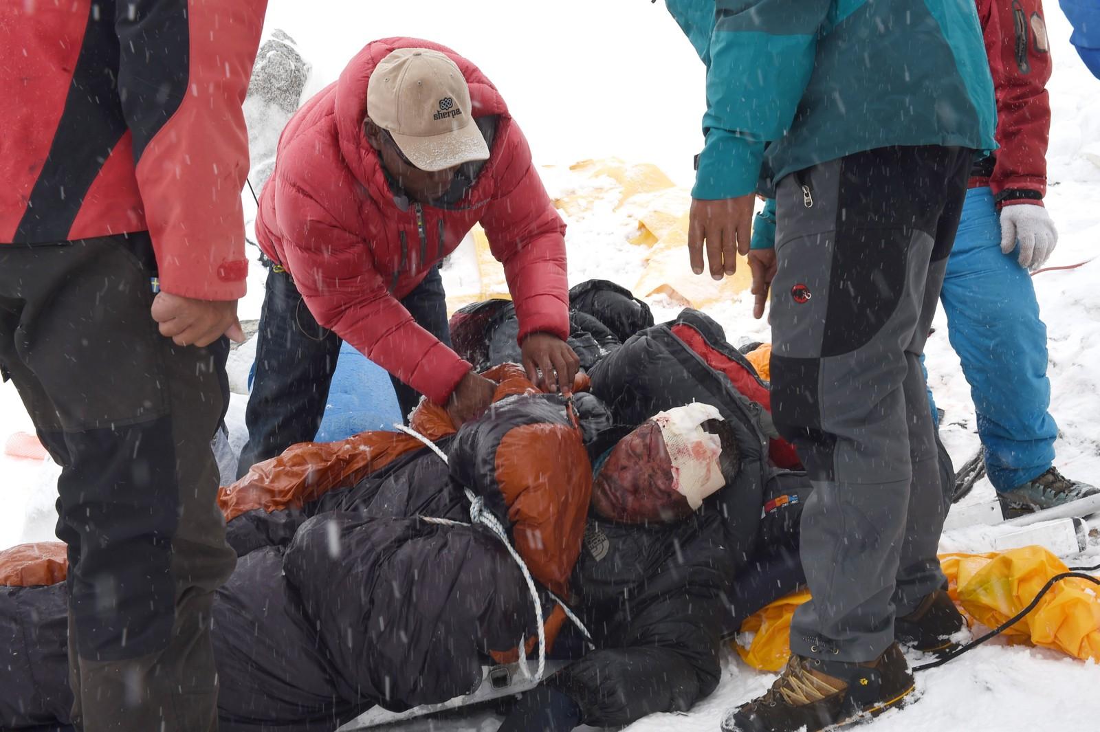 En hardt skadd sherpa får hjelp etter snøskredet på lørdag.