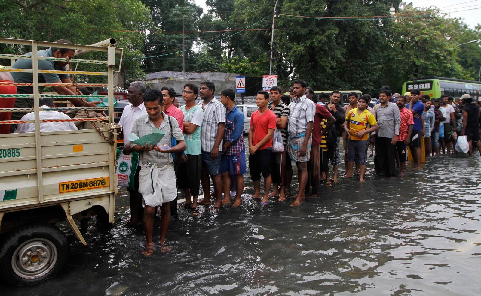 Flomrammede innbyggere i Chennai står i kø for å få mat av marinen. Dette er det kraftigste regnfallet på hundre år i delstaten Tamil Nadu i India.