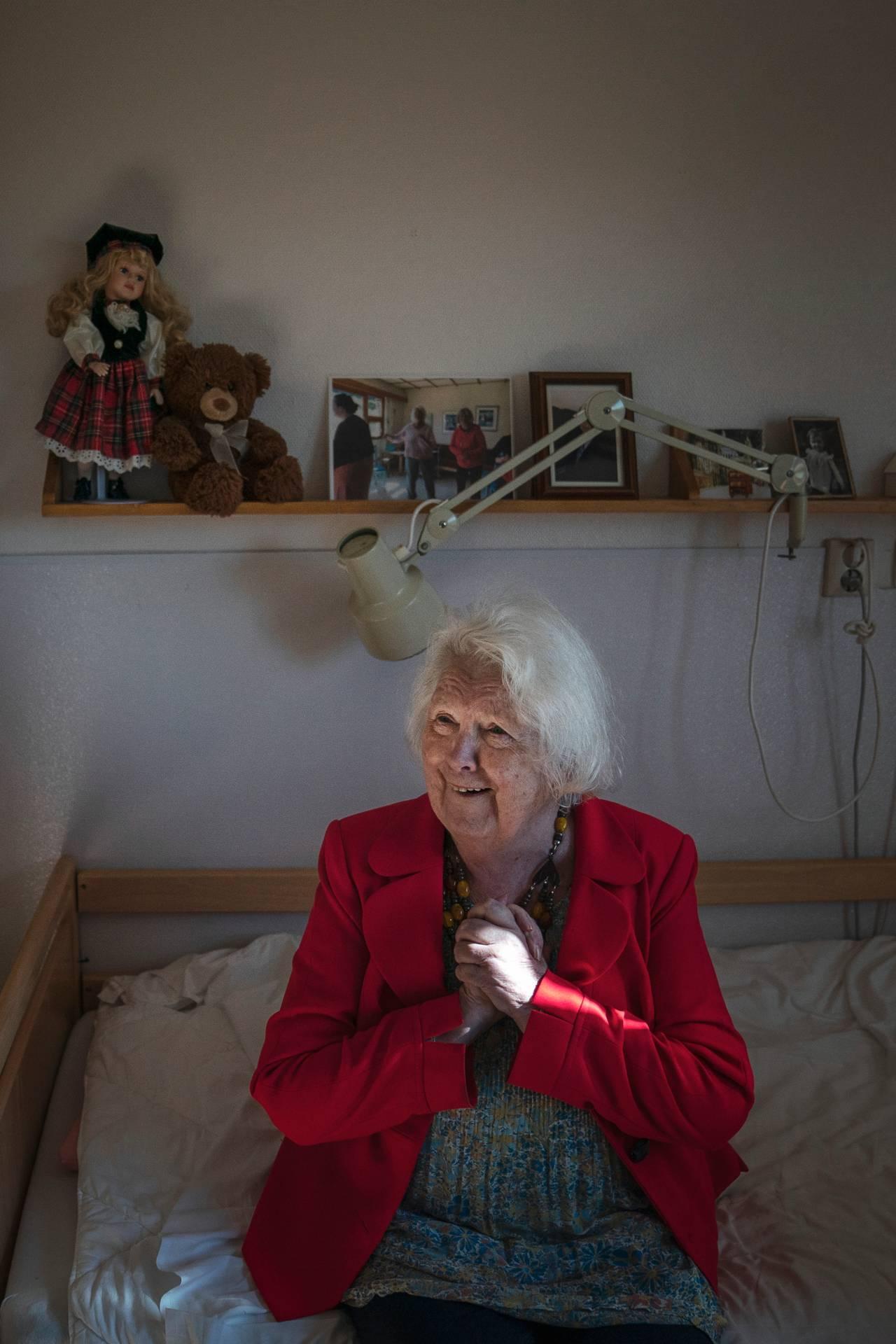 Kvinne i rød jakke sitter i seng og knytter hendene mens hun smiler stort. På veggen bak ser man en hylle med en rekke fotografier på en, en dukke og en teddybjørn.
