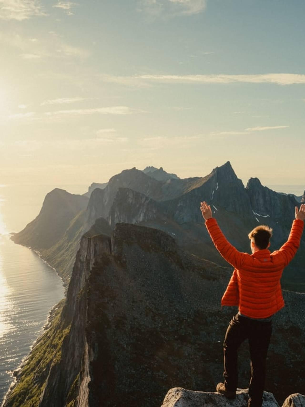 Mann strekker armene i været på toppen av fjell.