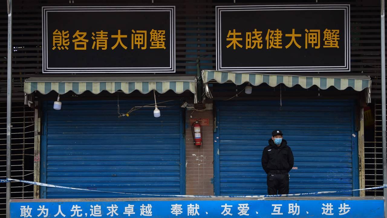 En sikkerhetsvakt står utenfor et fiskemarkedet i Wuhan hvor viruset ble oppdaget i januar.
