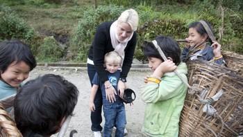 Kronprinsessa og prins Sverre Magnus ser på kniven barna i landsbyen skal skjære gras med
