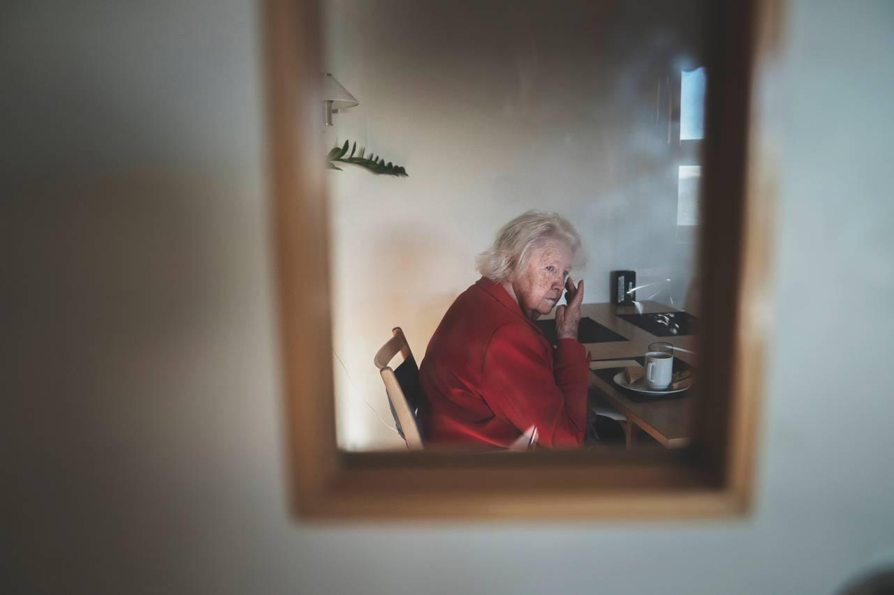 Anne Marie sitter ved frokostbordet og stirrer ut i rommet mens hånden strekkes opp til øynene.