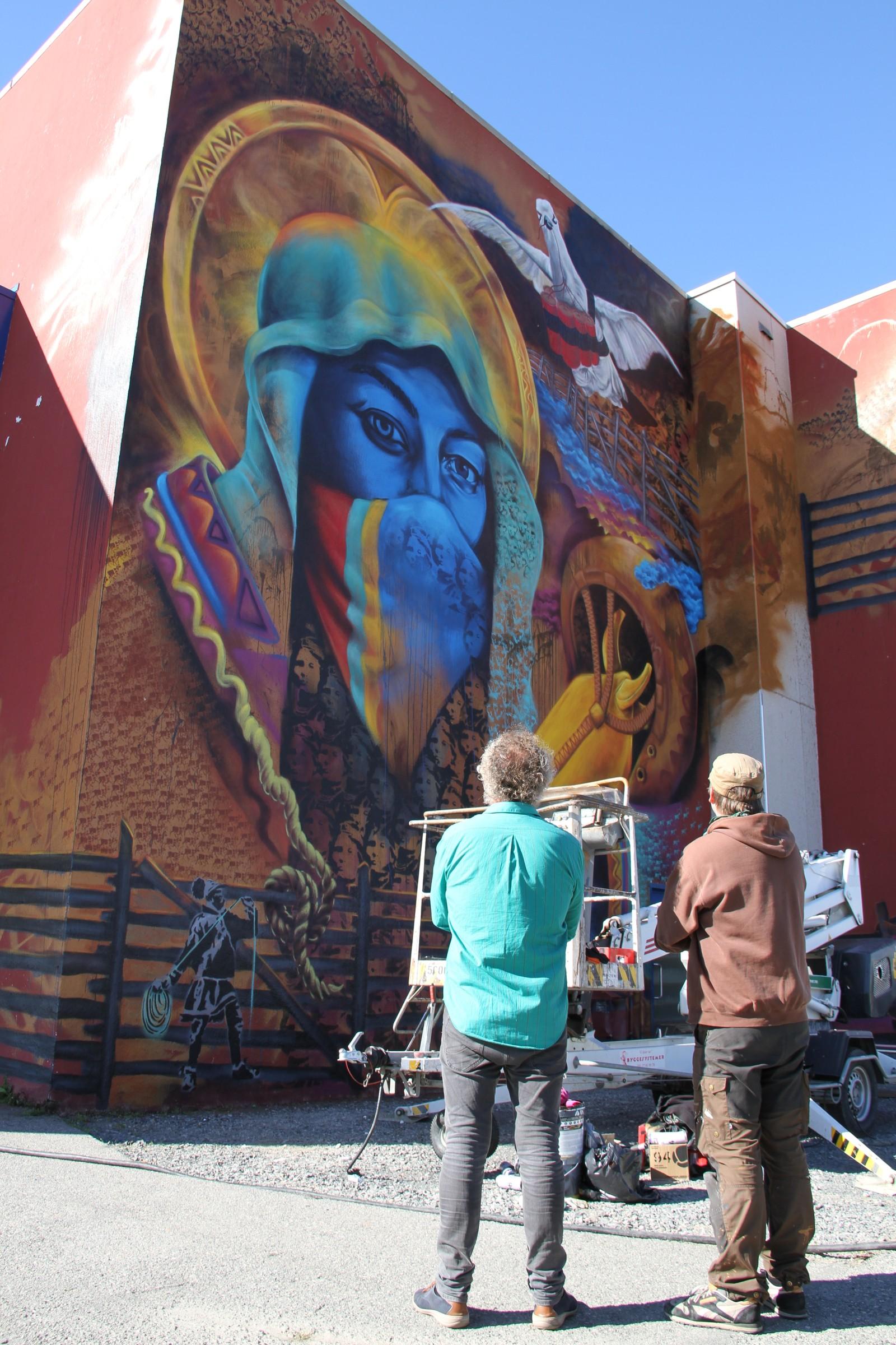 Leder for kultur i Alta kommune, Tor Helge Reinsnes Moen og kunstneren Anders Sunna studerer det ferdige verket på veggen til Alta ungdomskole.