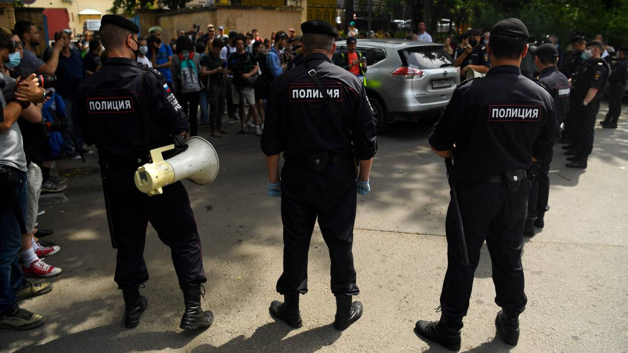 Police officers watch supporters of Ivan Safronov