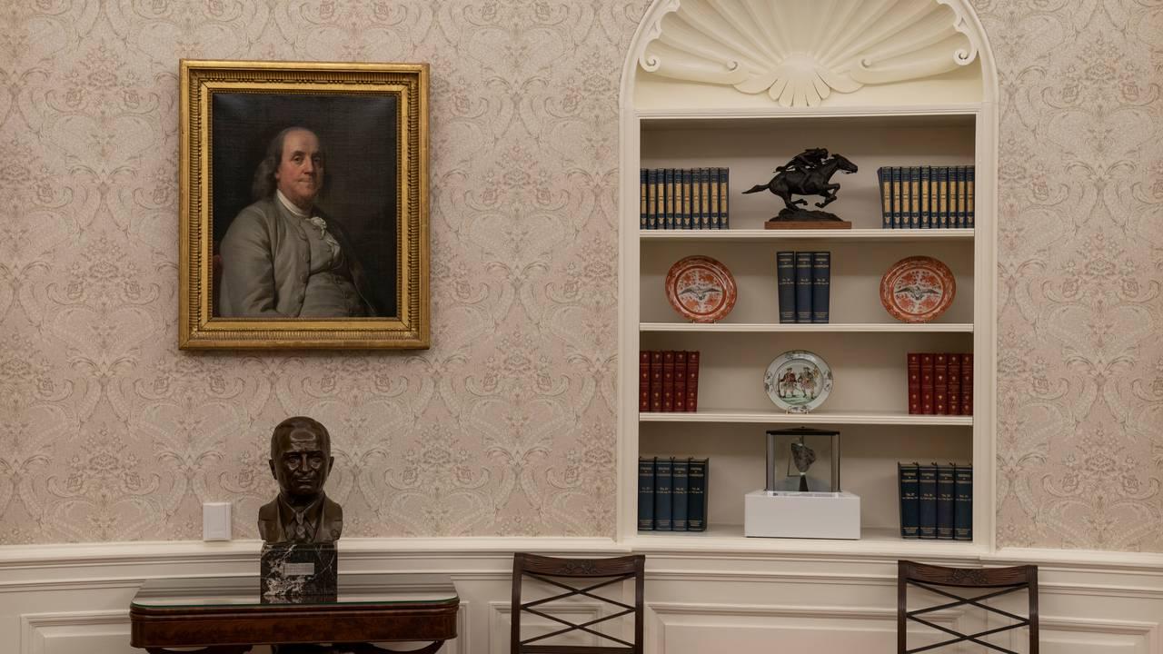 Det ovale kontor i Det hvite hus under Joe Biden. En byste av president Harry Truman står under et portrett av Benjamin Franklin. I bokhyllen står en stein fra månen (midten nederst).