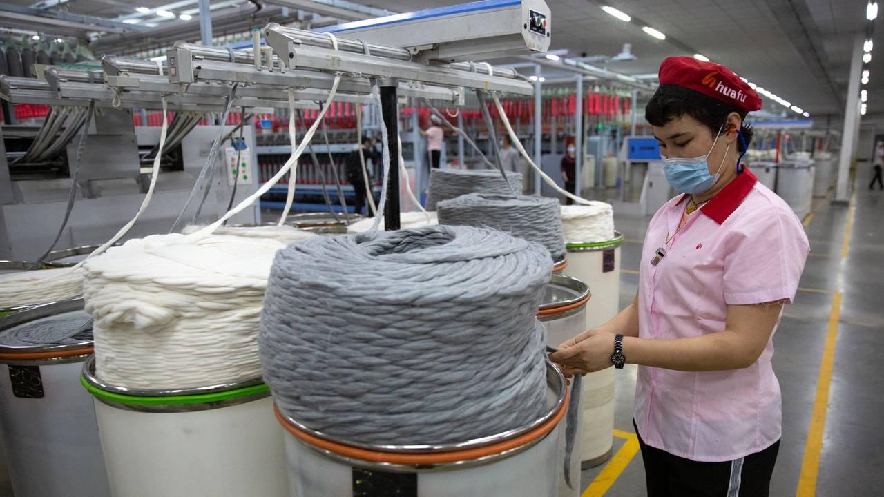 En arbeider sjekker produksjonen ved en bomullsfabrikk i Xinjiang Bildet er tatt 20. april 2021.