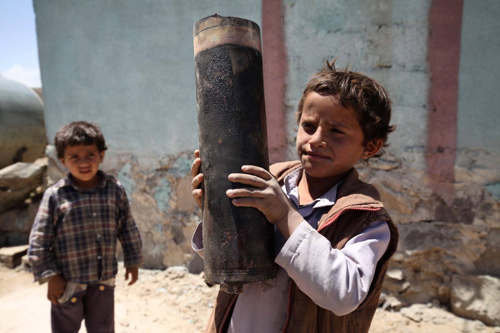 En gutt holder opp rester av en granat i utkanten av Jemens hovedstad Sana, 23. april, 2015. I mai var omtrent 300.000 internt fordrevne flyktninger i Jemen, skriver Unicef, og rundt 1500 var drept i konflikten.
