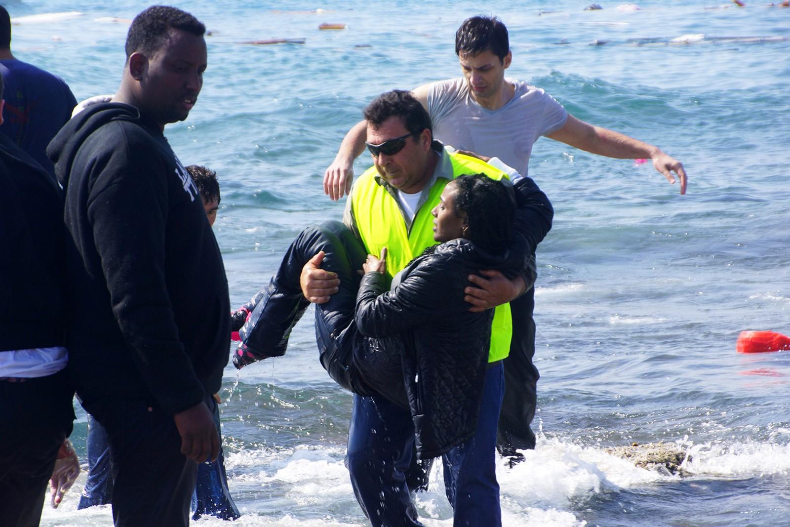 En mann redder en at de overlevende i havet utenfor den greske øya Rhodos.