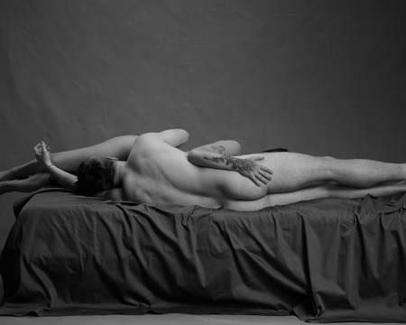 Et par ligger på siden med hodet mot hverandres kjønnsorgan på en svart seng. Begge er nakne. Mannen har mørkt hår og ligger med ryggen mot kamera. Kvinnen har mørkt hår og tatoveringer. De simulerer oral sex.