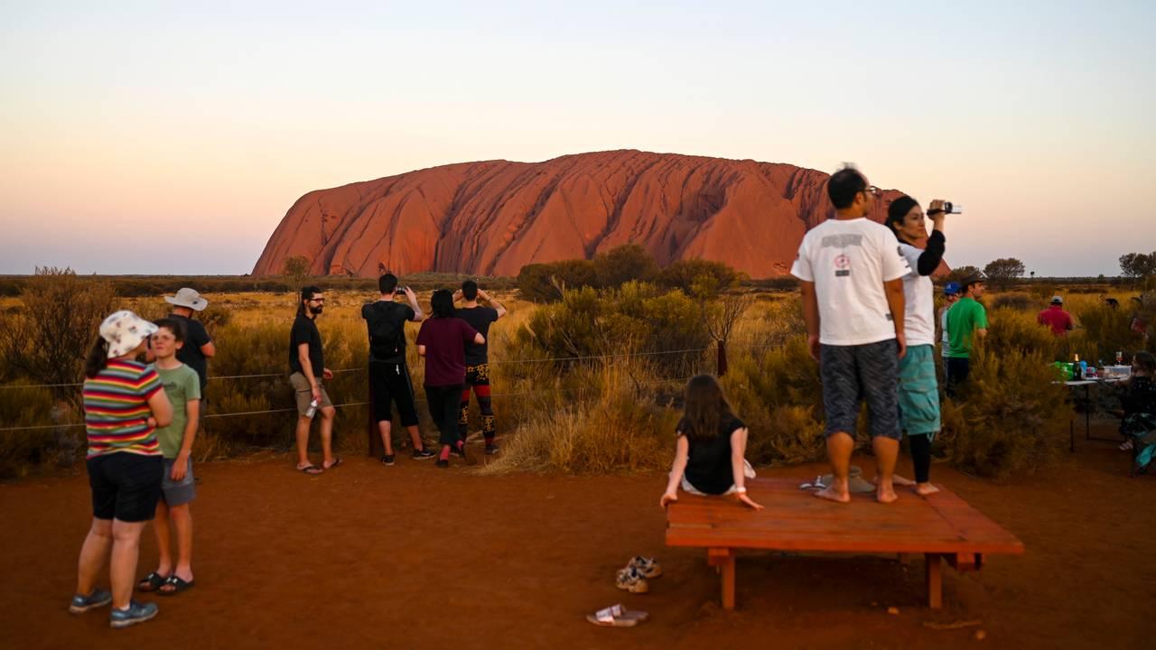 Turister ser på det karakteristiske fjellet Uluru i Australia.