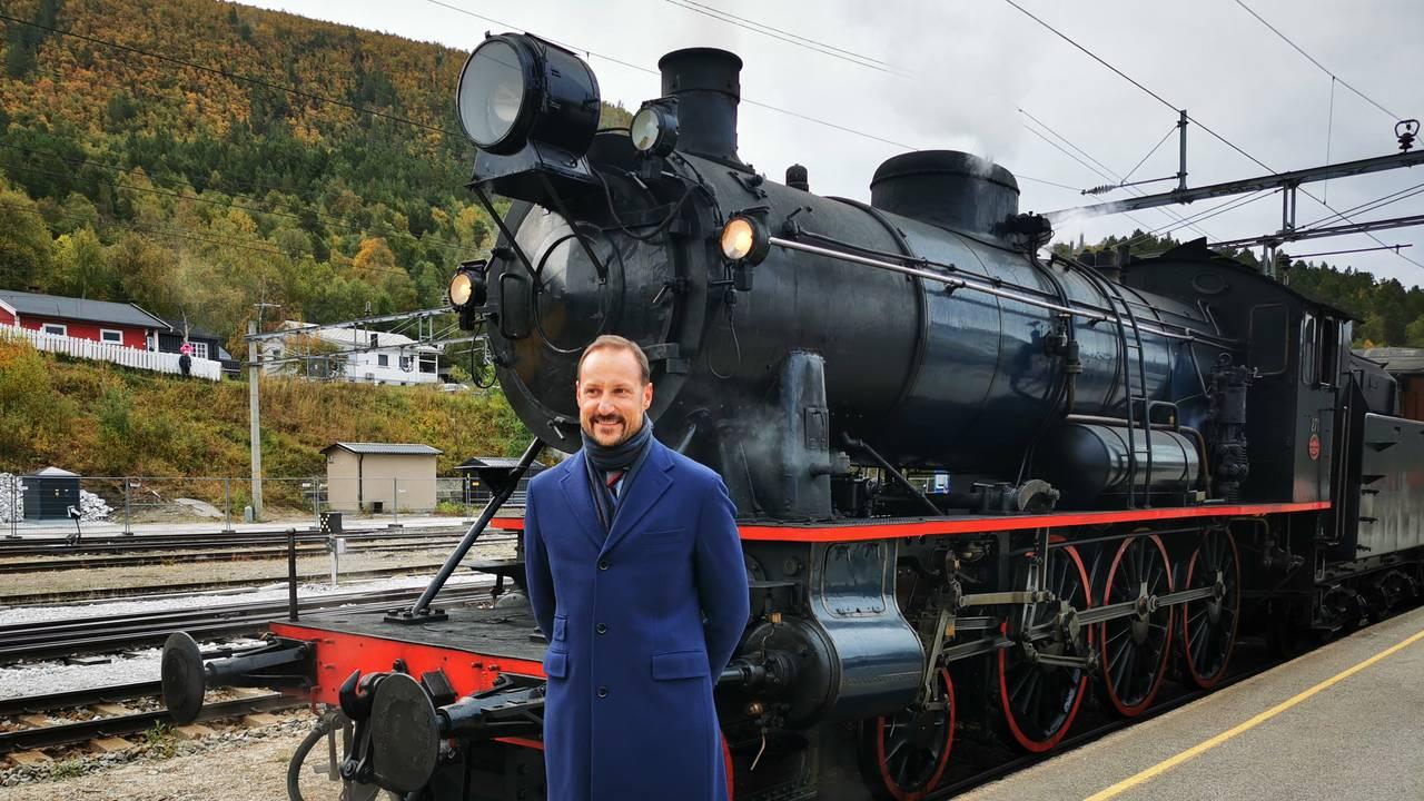 Kronprins Haakon Magnus foran et damptog på Dombås stasjon