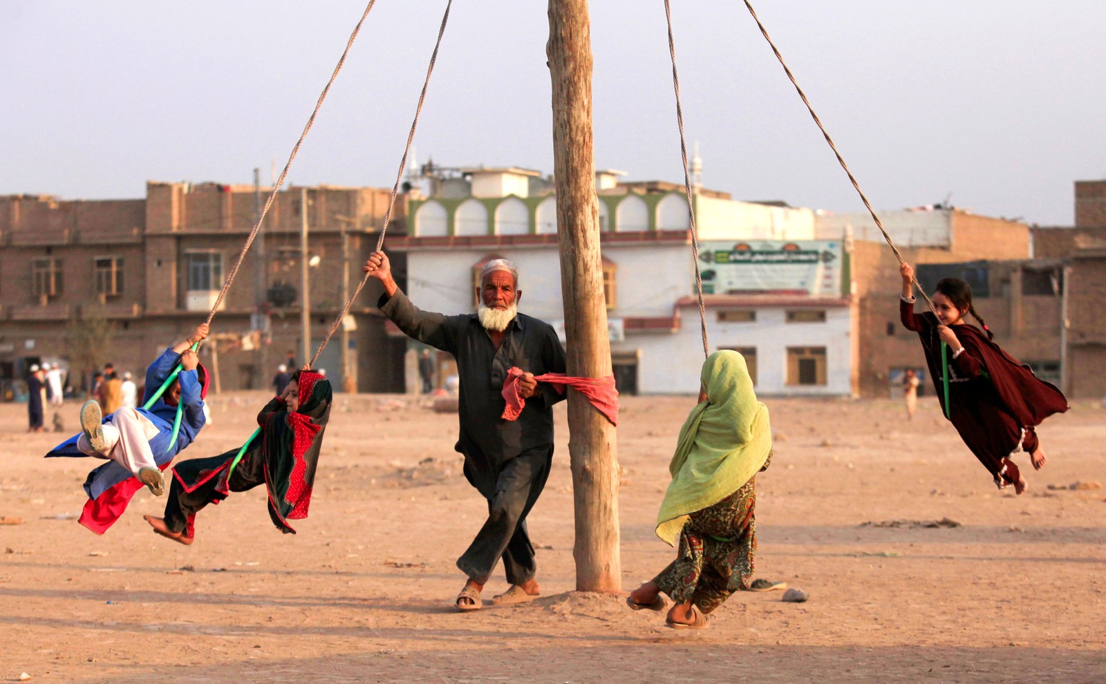 En mann snurrer barna rundt på en hjemmelaget karusell i Peshawar i Pakistan den 22. september.