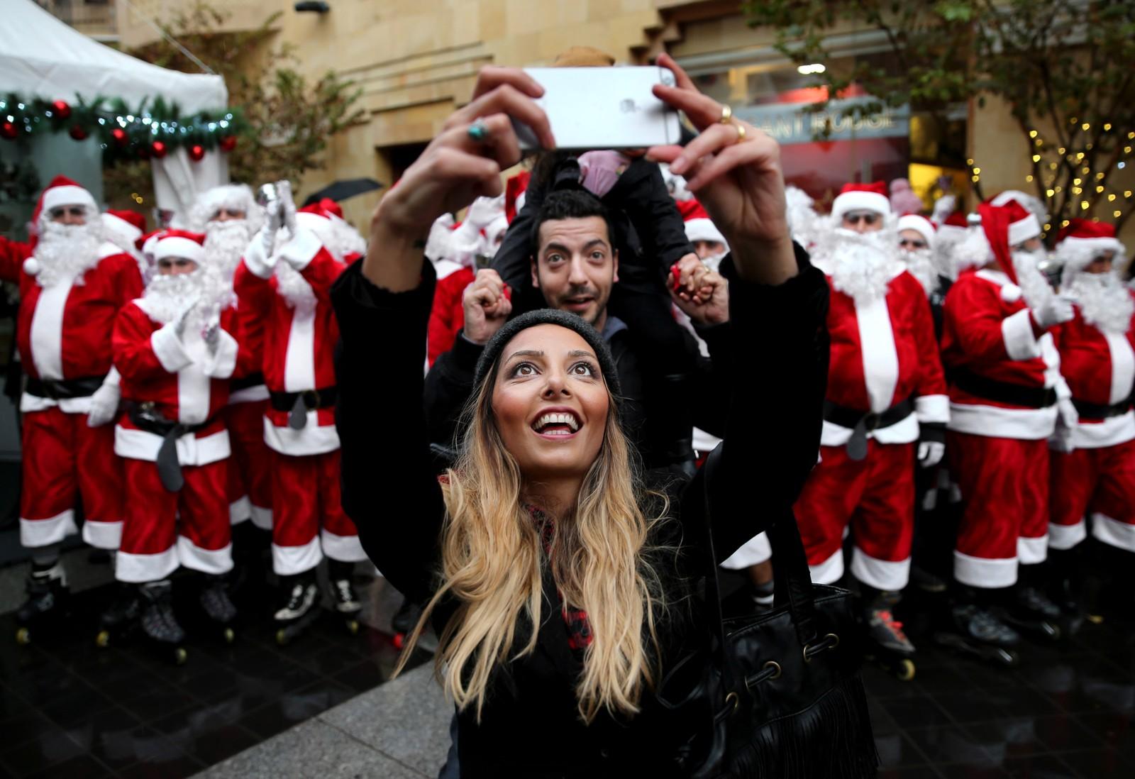 Et libanesisk par tar en selfie foran en gjeng nisser under en juleparade i Beirut, Libanon.