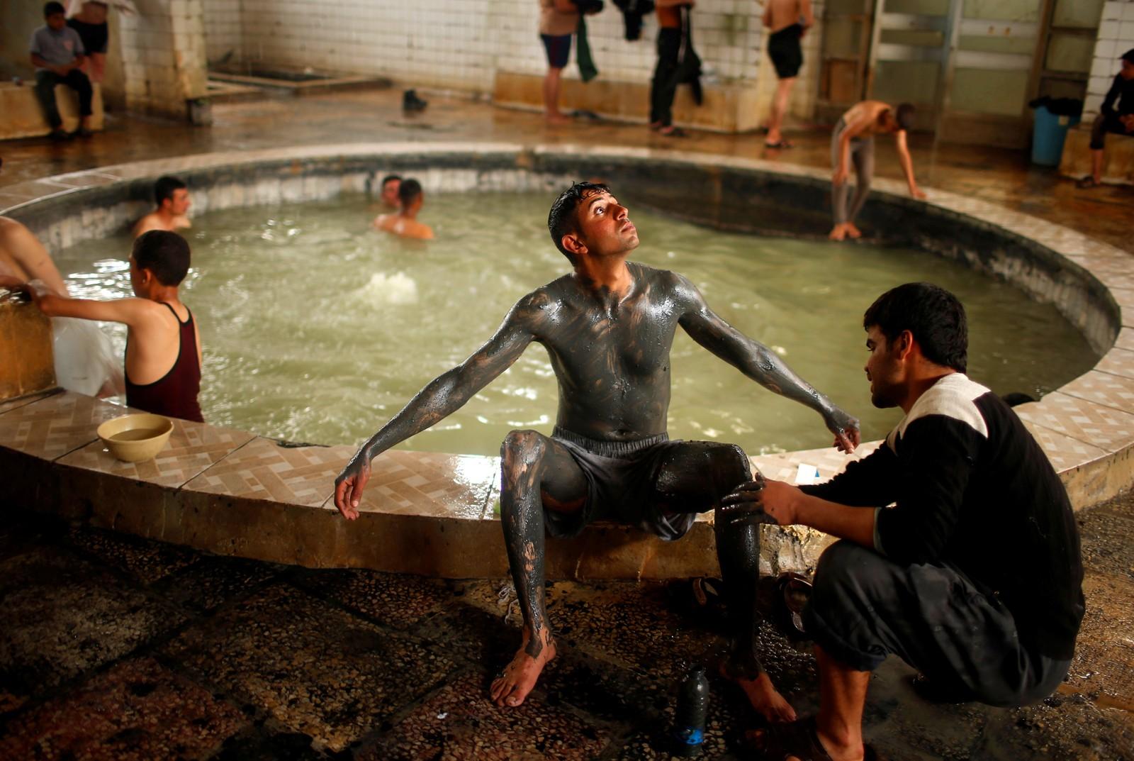 En irakisk ung mann får kroppen sin dekket med sand ved et svovelbad i Mosul i Irak.