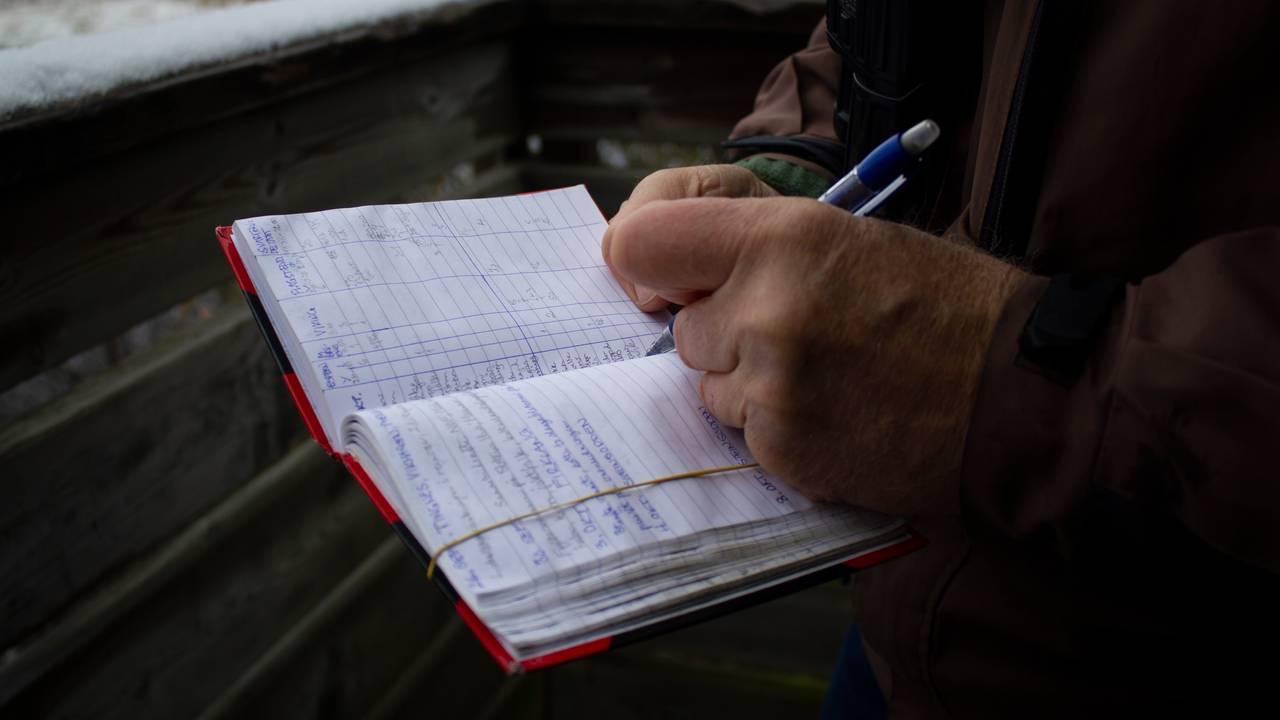 Biolog Jon Bekken skriver ned observasjonene sine i notatboka.