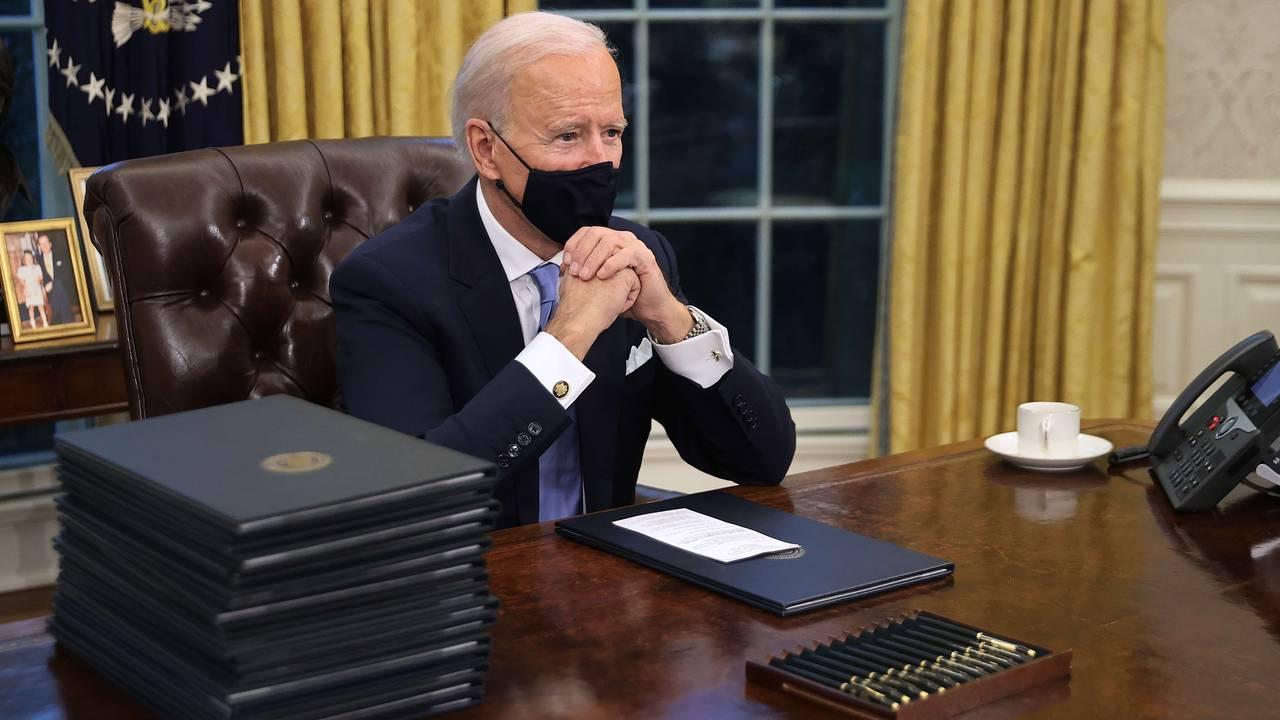 Joe Biden ved pulten med de mange pennene i Det hvite hus.