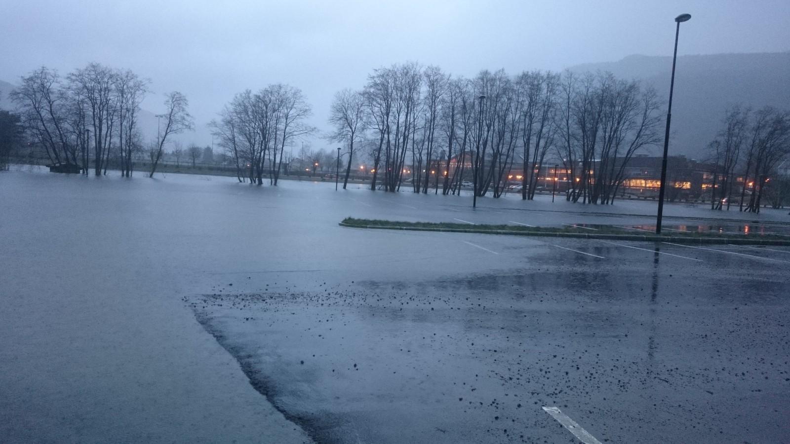 Parkeringsplassen ved Hafstadparken i Førde er full av vatn.