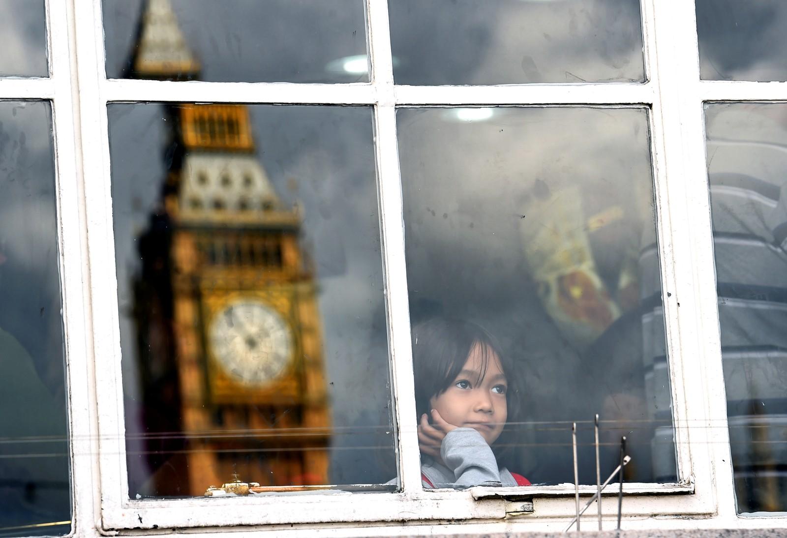 Et speilbilde av Big Ben, og en jente som ser mot klokketårnet.