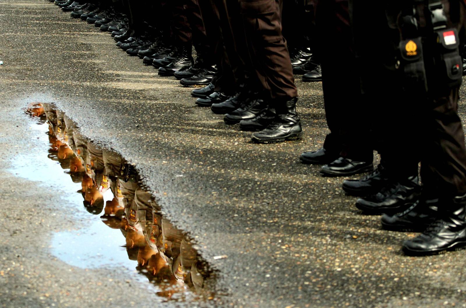 Politifolk står på rekke og rad under en seremoni før guvernørvalget i Lhokseumawe i Indonesia.