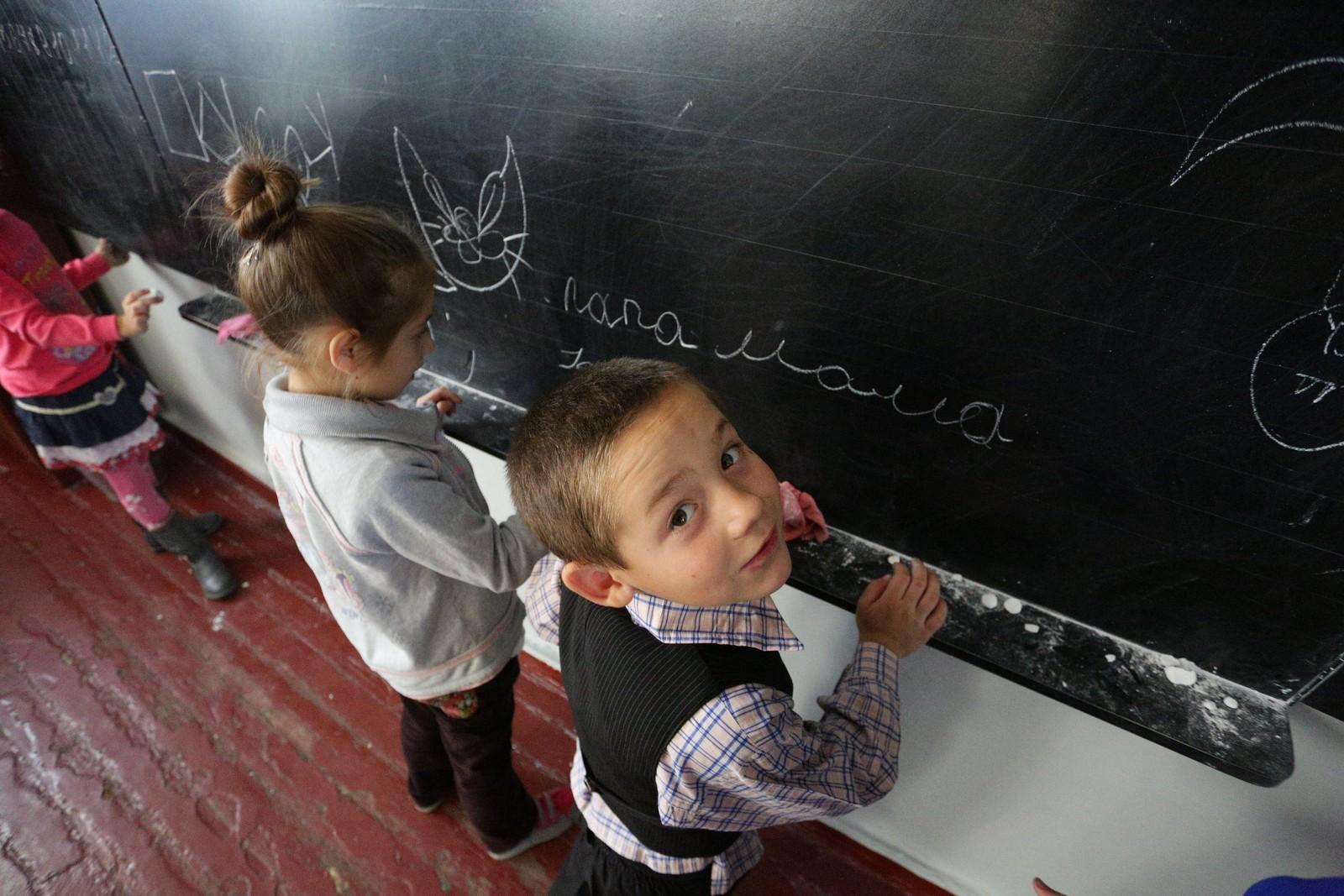 """Ukrainske barn i Staromykhailovka, i Donetsk-området, skriver """"far"""" og """"mor"""" på tavlen. Unicef har beregnet at over 1,7 millioner barn er påvirket av konflikten i Øst-Ukraina."""