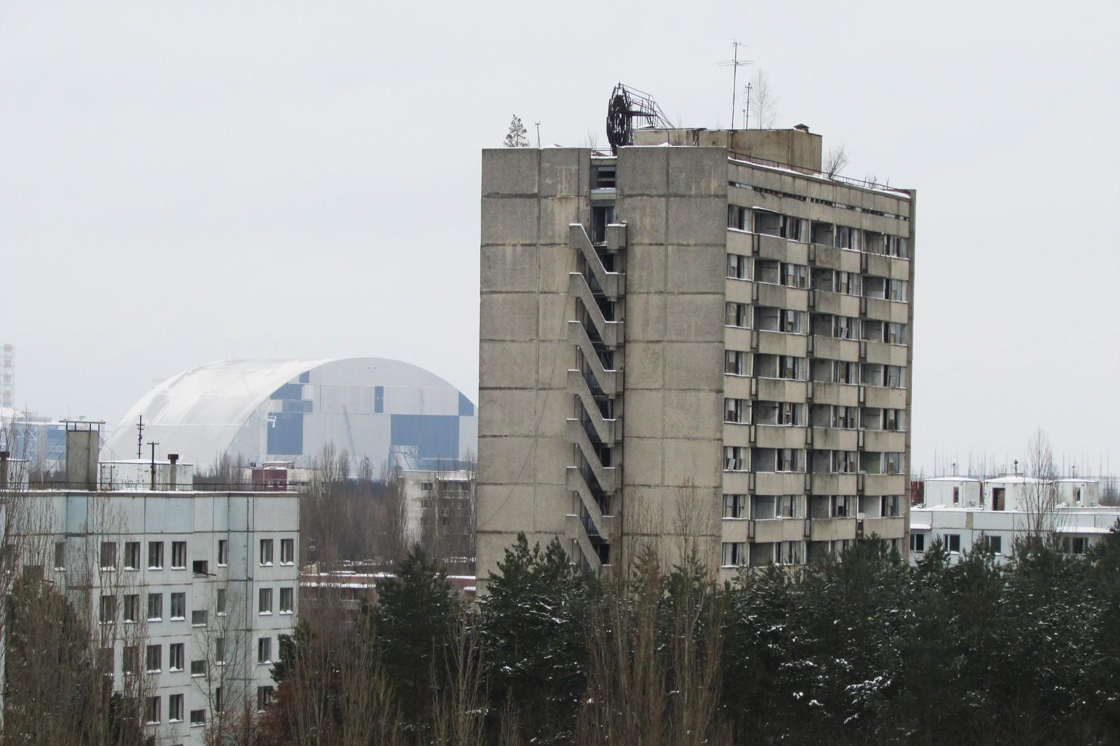 Den nye stålsarkofagen som skal dekke Reaktor nummer fire sees fra takene til mange av bygningene.