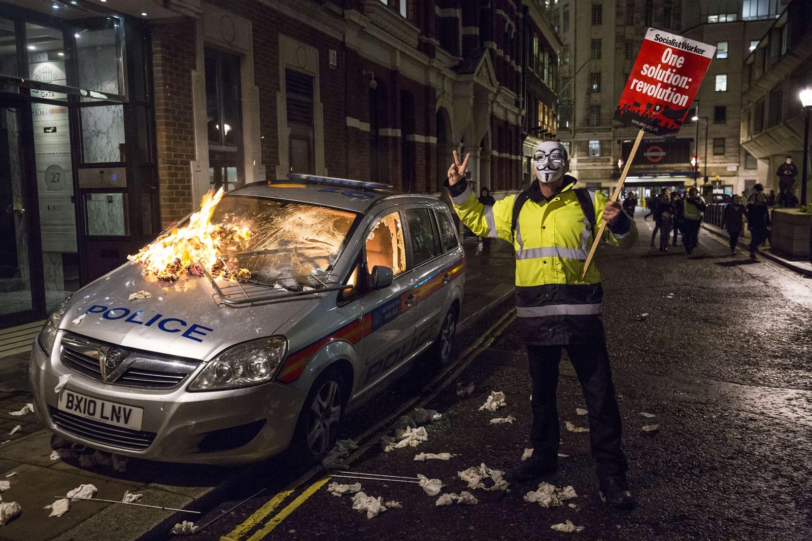 """En demonstrant med Guy Fawkes-maske står ved siden av en brennende politibil under """"Million Masks March"""", arrangert av hacker-gruppa Anonymous.  Guy Fawkes er mannen som prøvde å sprenge det britiske parlamentet i 1605, noe som 5. november hvert år."""
