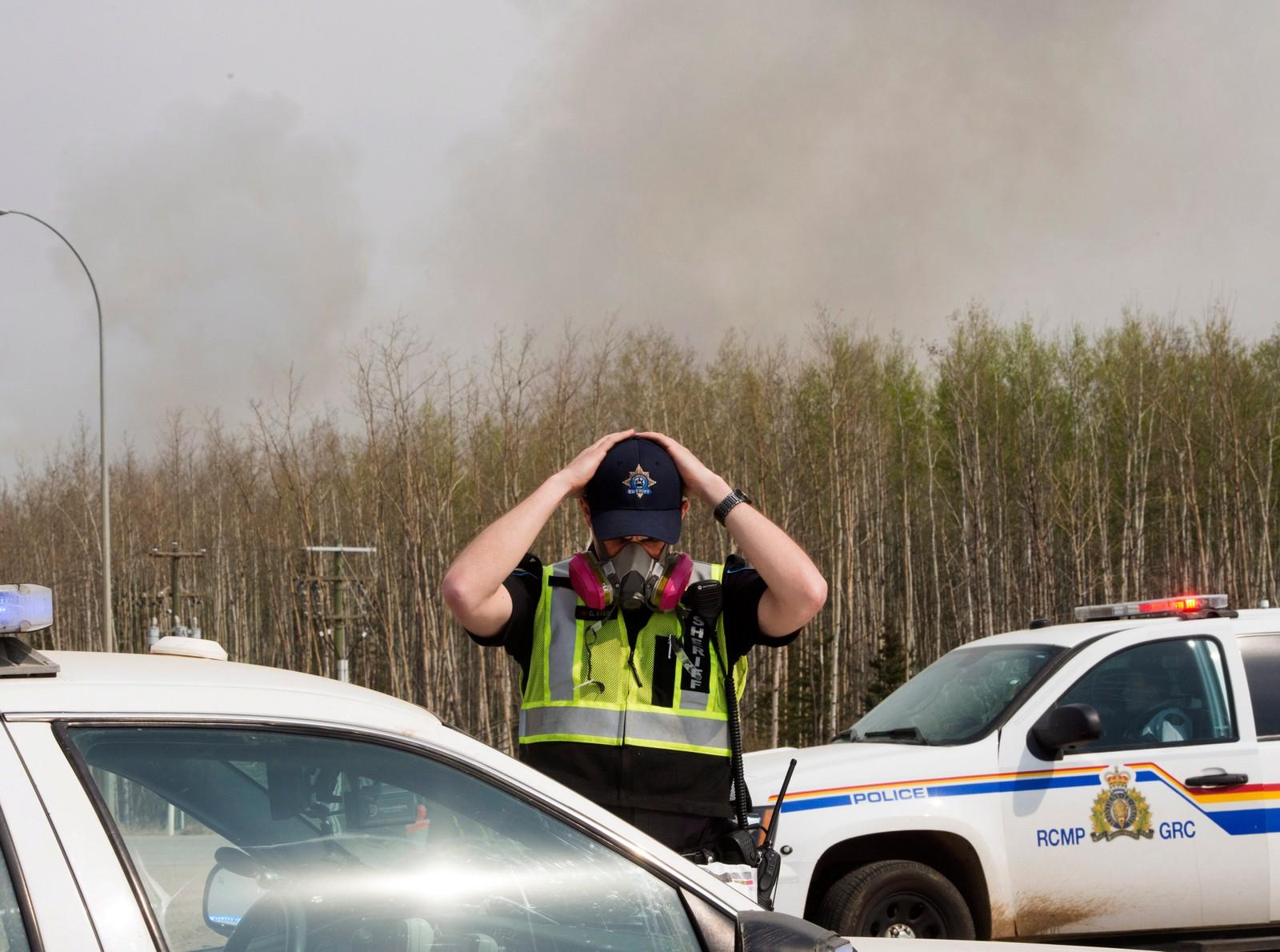 En politimann tar på seg en gassmaske mot røyken fra skogbrannen i Alberta, Canada.