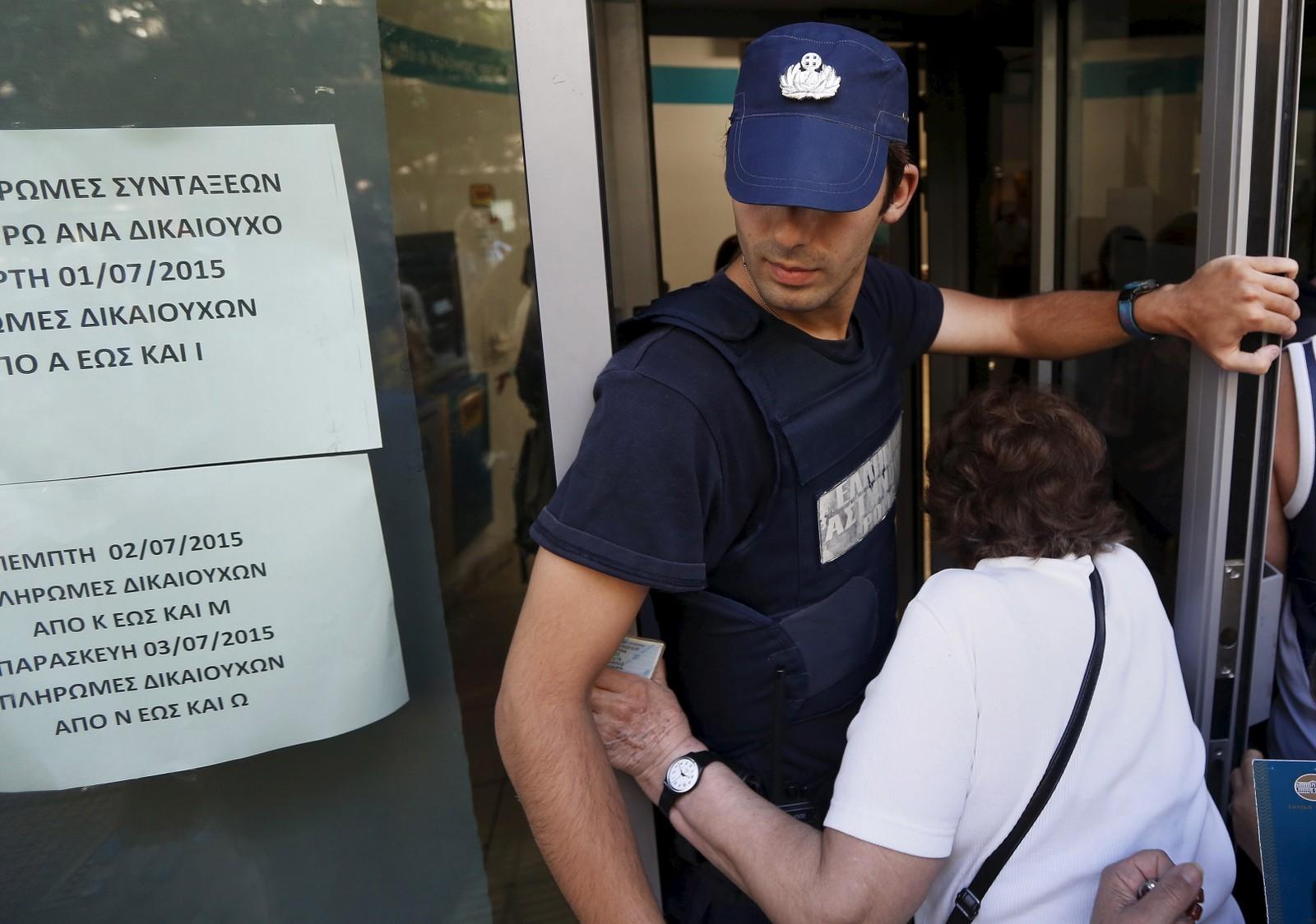 En kvinne smyger seg inn døren til en bank i Aten, mens en politimann forsøker å holde orden på køen og mengden av eldre grekere som venter på tur på å få komme inn.
